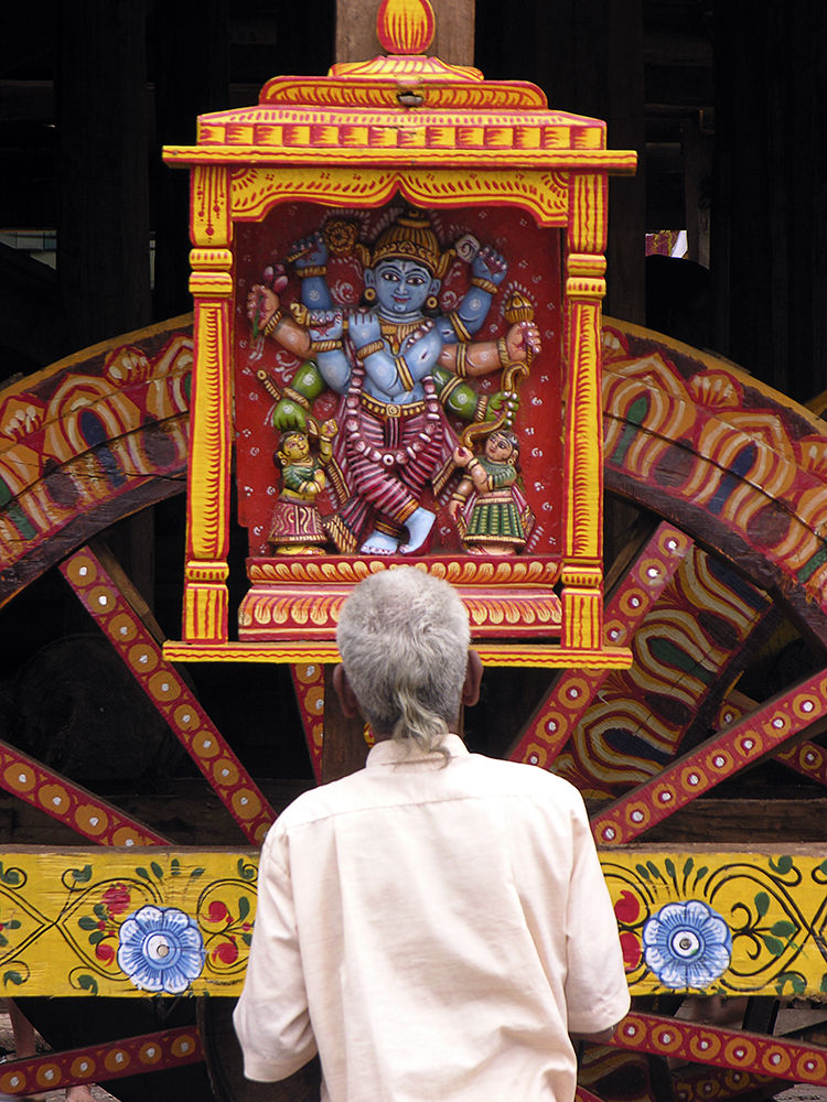 A devotee prays to an image of Krishna on the side of one of the chariots