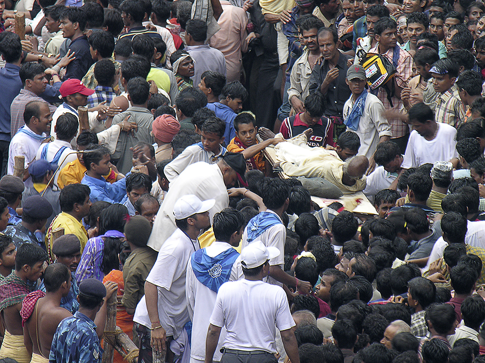 An injured man is carried away through the crowds