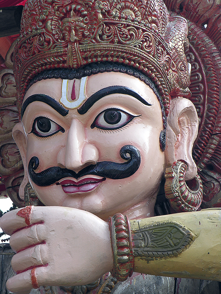 A large brightly coloured wooden deity adorning one of the chariots
