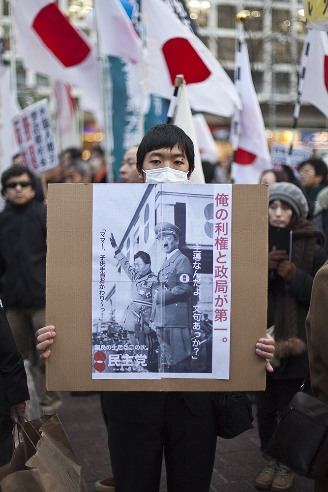 Protestor holding shocking photoshoped poster comparing Mr Ozawa and Mr Hatoyama to Hitler and the Nazis